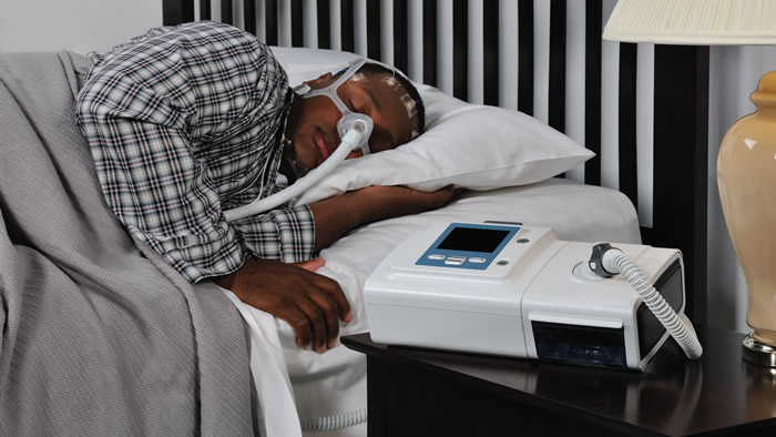 Man sleeping using CPAP machine